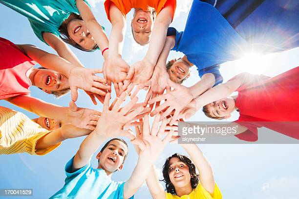 Kids with hands in middle against the sky
