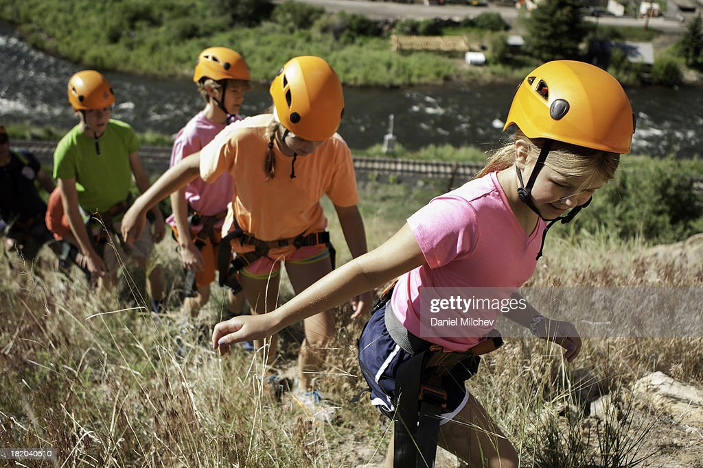 Kids with helmets hikinh up the mountain. : Stock Photo