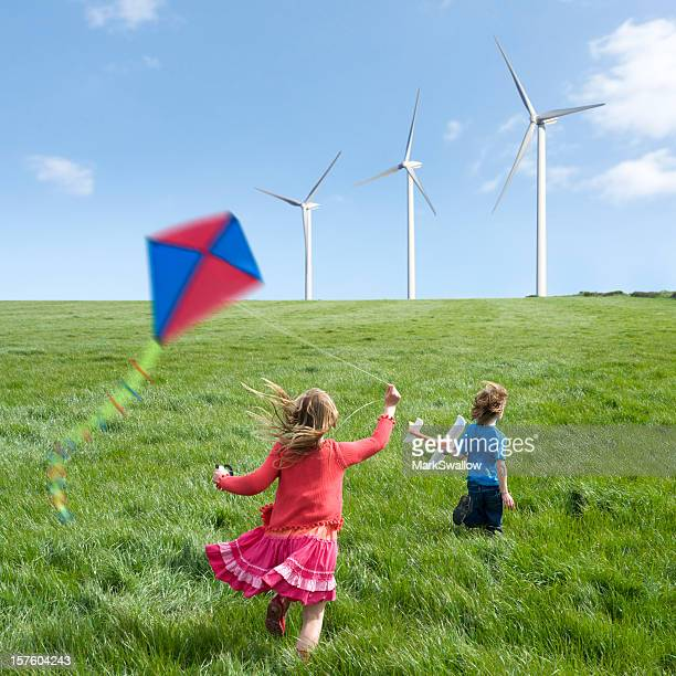 Kids with kites running towards wind turbines