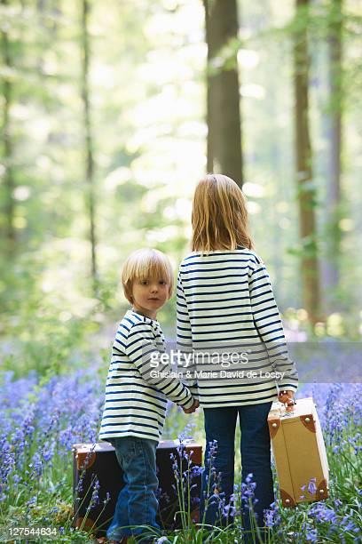 Bambini con i bagagli nel campo di fiori
