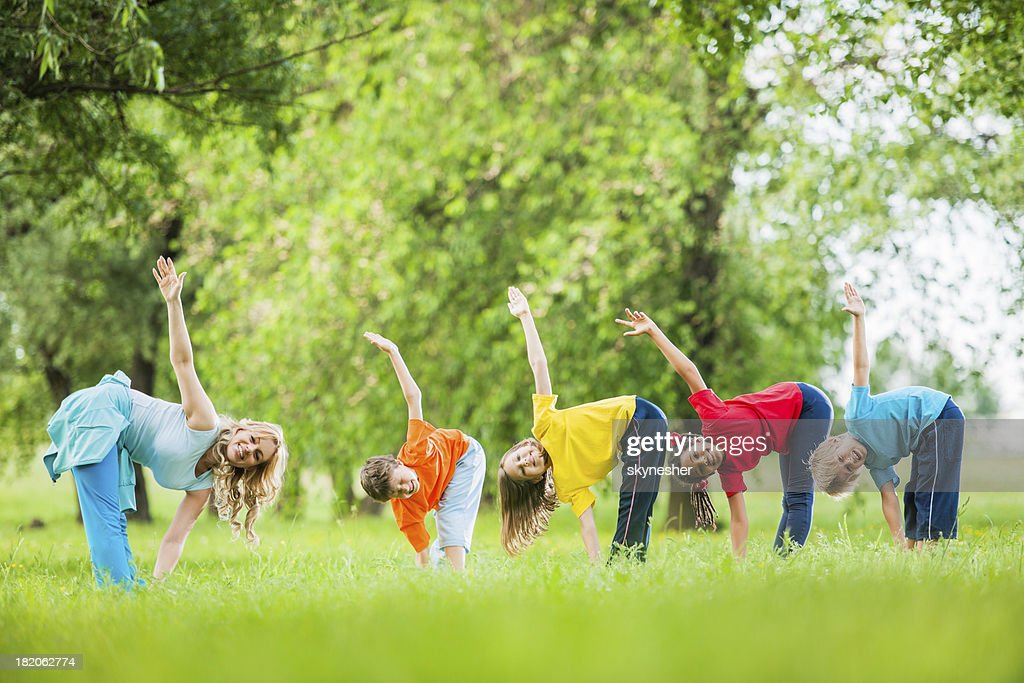 Kids with their PE teacher exercising outdoors.