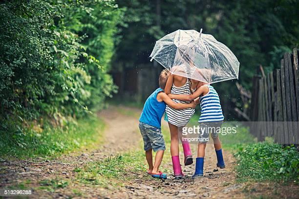 Bambini con ombrello godersi la pioggia.