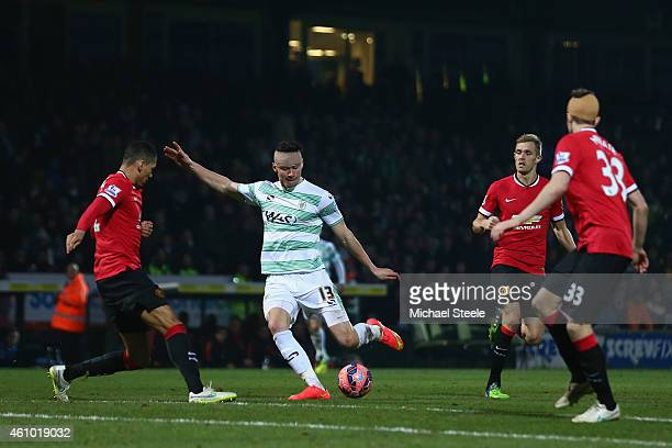 Kieffer Moore of Yeovil Town shoots as Chris Smalling of Manchester United closes in during the FA Cup Third Round match between Yeovil Town and...