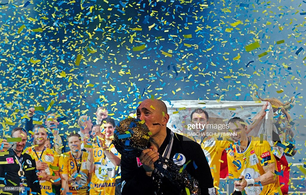Kielce's headcoach Talant Dujshebaev celebrates with the trophy after winning the Handball EHF Champions League final Four Final match between KS Vive Tauron Kielce and MVM Veszprém in Cologne, western Germany, on May 29, 2016. / AFP / SASCHA