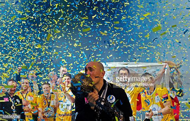 TOPSHOT Kielce's headcoach Talant Dujshebaev celebrates with the trophy after winning the Handball EHF Champions League final Four Final match...