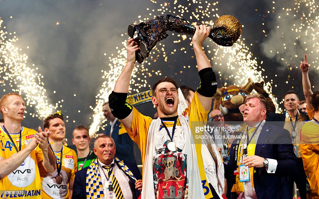 Kielce's Julen Aguinagalde celebrates with the trophy and teammates after winning the Handball EHF Champions League final Four Final match between KS Vive Tauron Kielce and MVM Veszprém in Cologne, western Germany, on May 29, 2016. / AFP / SASCHA
