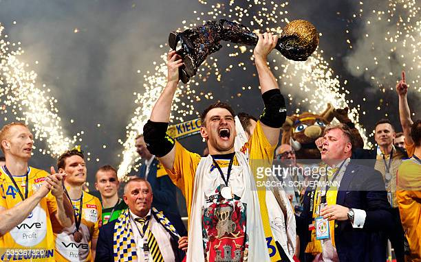 Kielce's Julen Aguinagalde celebrates with the trophy and teammates after winning the Handball EHF Champions League final Four Final match between KS...