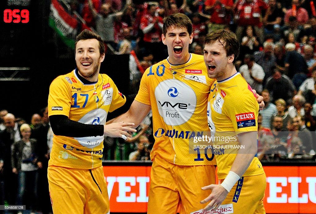 Kielce's Manuel Strlek, Mateusz Kus and a teammate celebrate after the Handball EHF Champions League final Four semi final match between KS Vive Tauron Kielce and Paris St-Germain in Cologne, western Germany, on May 28, 2016. / AFP / SASCHA