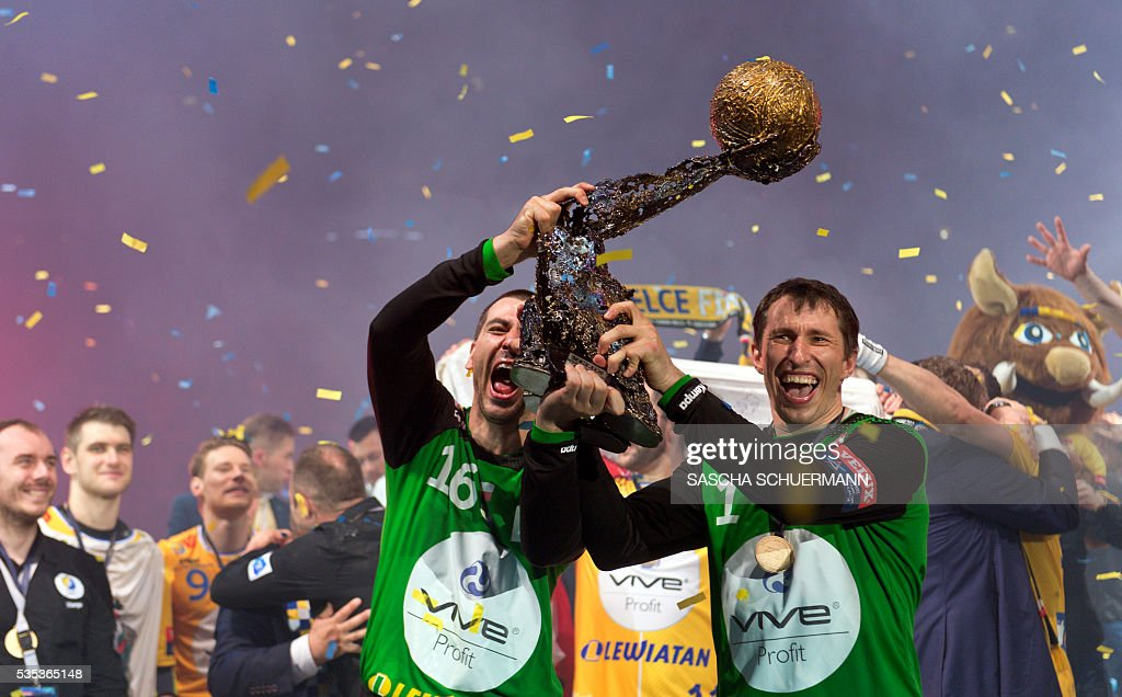 Kielce's Marin Sego (L) and Slawomir Szmal celebrate with the trophy after winning the Handball EHF Champions League final Four Final match between KS Vive Tauron Kielce and MVM Veszprém in Cologne, western Germany, on May 29, 2016. / AFP / SASCHA