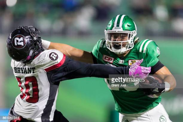 Kienan LaFrance of the Saskatchewan Roughriders gives a straight arm to Serderius Bryant of the Ottawa Redblacks during a run in the first half of...