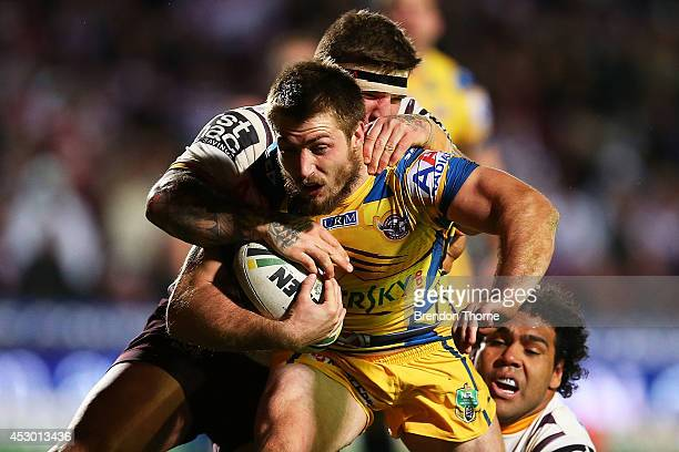 Kieran Foran of the Sea Eagles is tackled by Josh McGuire and Sam Thaiday of the Broncos during the round 21 NRL match between the ManlyWarringah Sea...