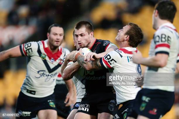 Kieran Foran of the Warriors is tackled by Jake Friend and Shaun KennyDowall of the Roosters during the round nine NRL match between the New Zealand...