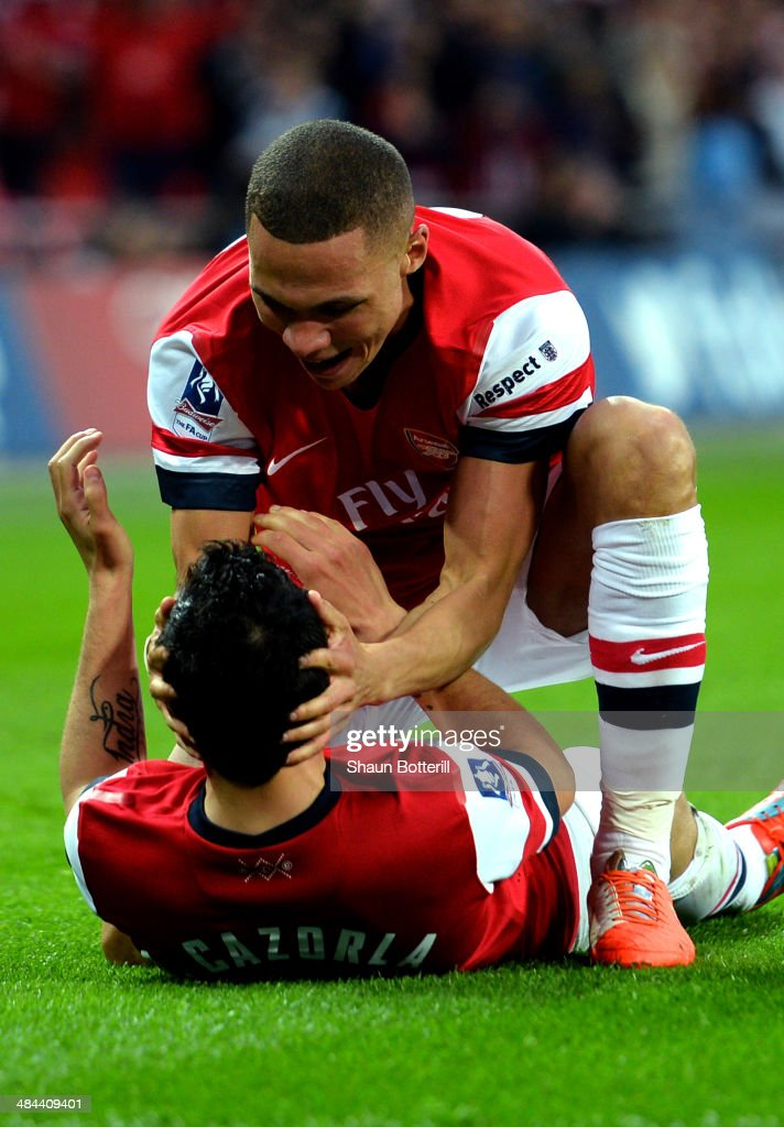 Kieran Gibbs of Arsenal congratulates Santi Cazorla of Arsenal on scoring the winning penalty during the FA Cup Semi-Final match between Wigan Athletic and Arsenal at Wembley Stadium on April 12, 2014 in London, England.