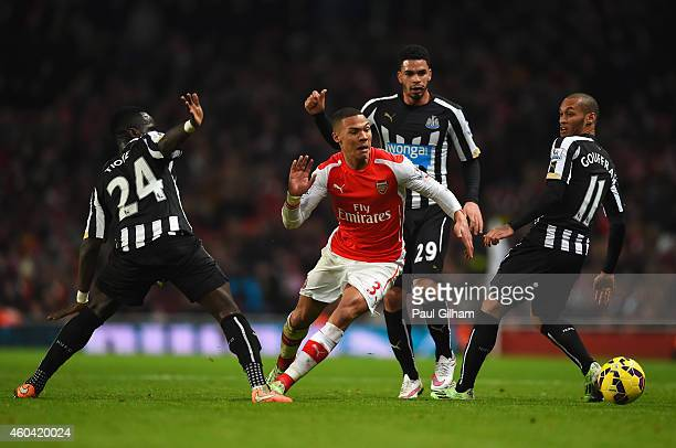Kieran Gibbs of Arsenal goes past Cheik Ismael Tiote Emmanuel Riviere and Yoan Gouffran of Newcastle United during the Barclays Premier League match...