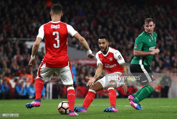 Kieran Gibbs of Arsenal passes to Theo Walcott of Arsenal as he scores the first goal during The Emirates FA Cup QuarterFinal match between Arsenal...