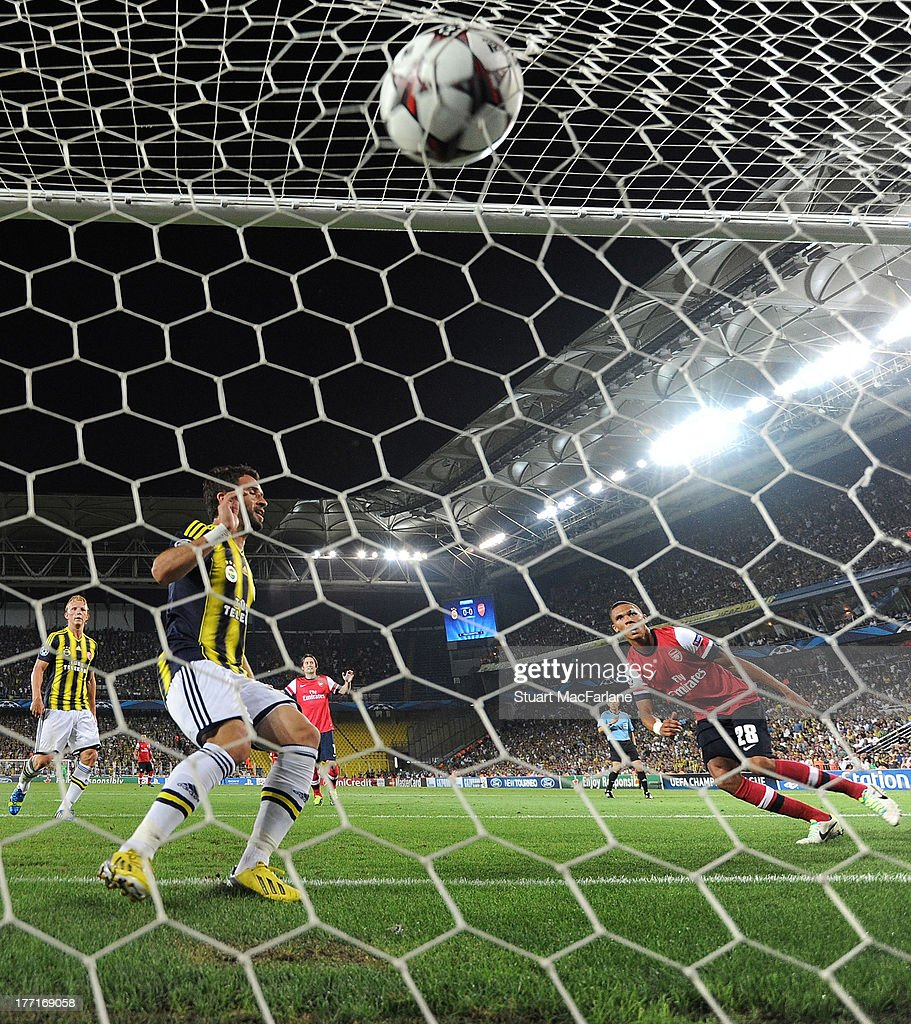 Kieran Gibbs shoots past Fenerbahce defender Gokhan Gonul to score the 1st Arsenal goal during the UEFA Champions League Play Off first leg match between Fenerbache SK and Arsenal FC at Sukru Saracoglu Stadium on August 21, 2013 in Istanbul, Turkey.