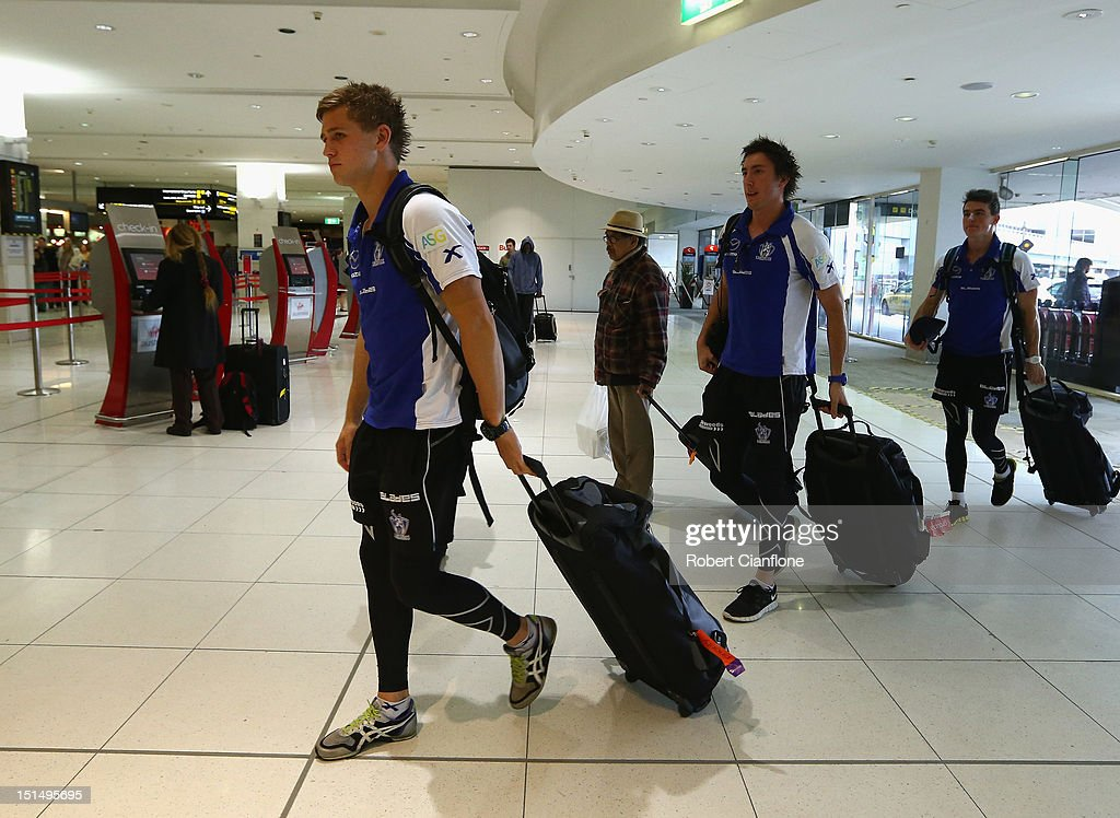 Kieran Harper, Samuel Wright and Aaron Mullett of the North Melbourne Kangaroos arrive at Melbourne Airport on September 7, 2012 in Melbourne, Australia.
