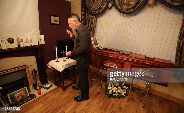 Kieran Megraw the brother of IRA victim Brendan Megraw poses lighting a candle with the coffin of his brother and a photograph after his remains were...