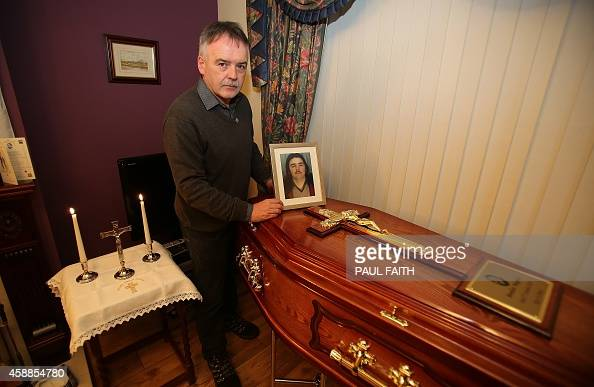Kieran Megraw the brother of IRA victim Brendan Megraw poses with the coffin of his brother and a photograph after his remains were brought to his...