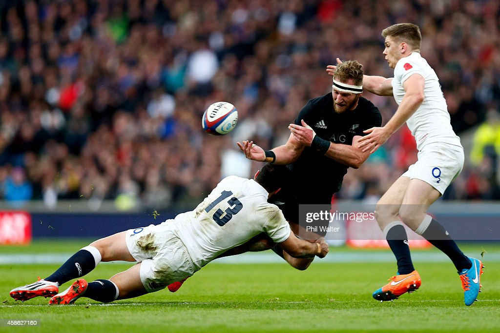 Kieran Read of New Zealand offloads the ball as he is tackled by Brad Barritt and Owen Farrell of England during the QBE International match between...