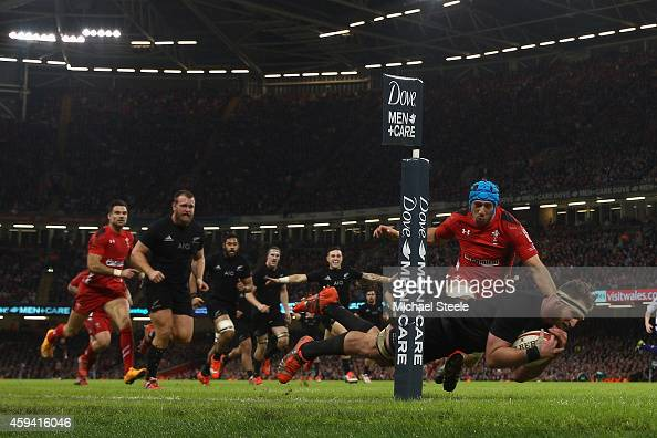 Kieran Read of the All Blacks scores his sides fourth try despite the attentions of Justin Tipuric of Wales during the International match between...