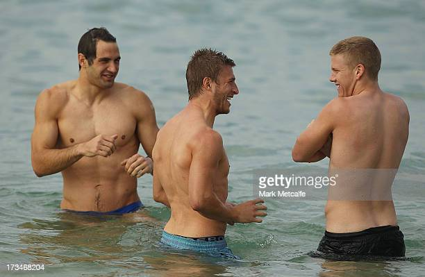 Kieren Jack Josh Kennedy and Daniel Hannebery wade in the ocean during a Sydney Swans AFL recovery session at Coogee Beach on July 15 2013 in Sydney...