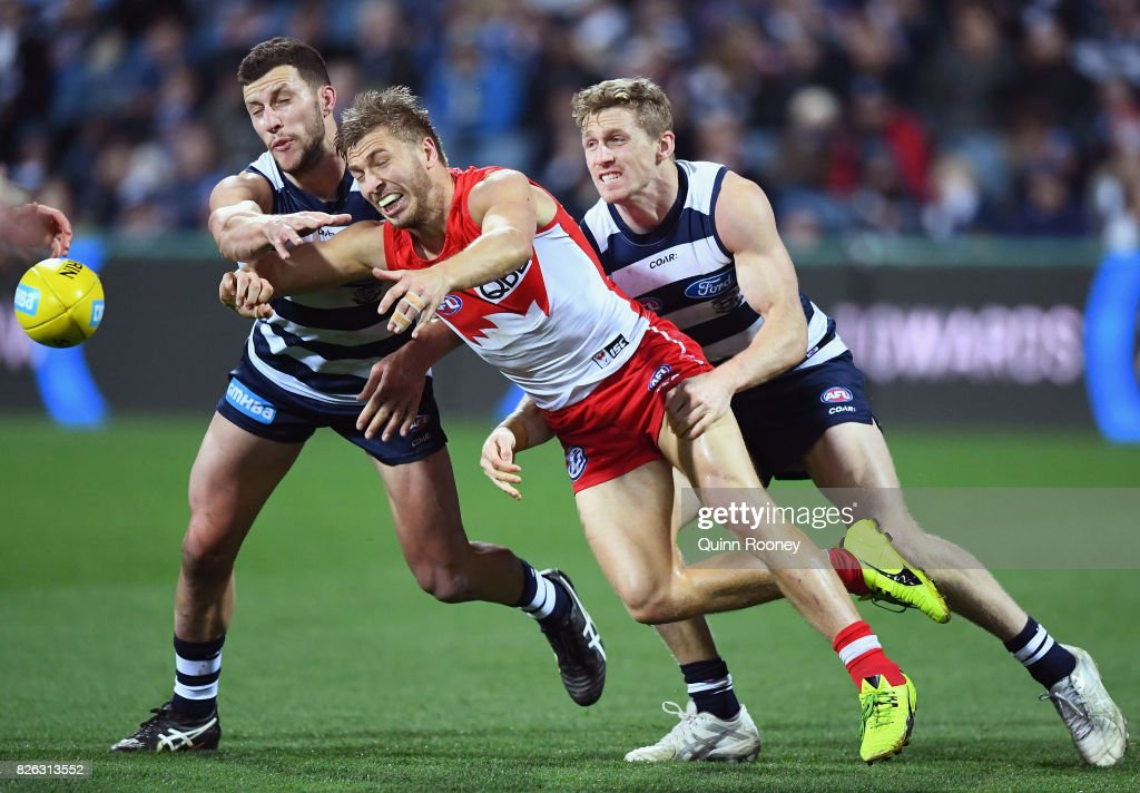 Kieren Jack of the Swans handballs whilst being tackled by Sam Menegola and Scott Selwood of the Cats during the round 22 AFL match between the Geelong Cats and the Sydney Swans at Simonds Stadium on August 4, 2017 in Geelong, Australia.