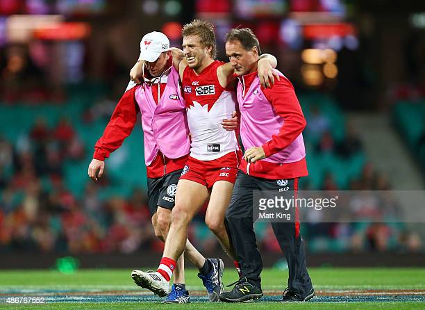 Kieren Jack of the Swans is assisted from the field after sustaining an injury during the round 23 AFL match between the Sydney Swans and the Gold...