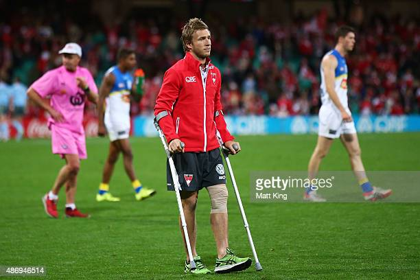 Kieren Jack of the Swans waits on the field on crutches at fulltime after sustaining an injury during the round 23 AFL match between the Sydney Swans...