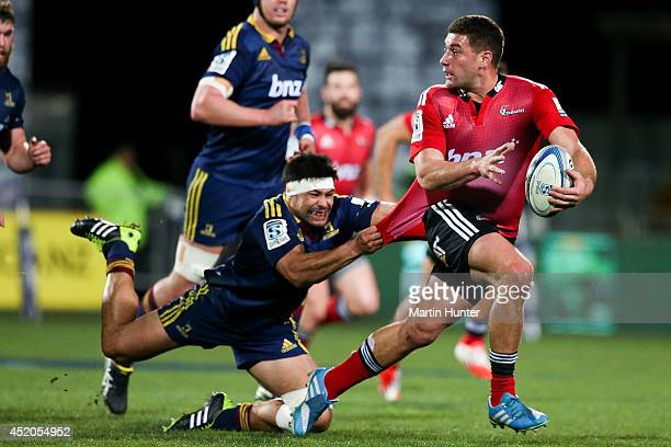 Kieron Fonotia of the Crusaders breaks away from the tackle of Shane Christie of the Highlanders during the round 19 Super Rugby match between the...