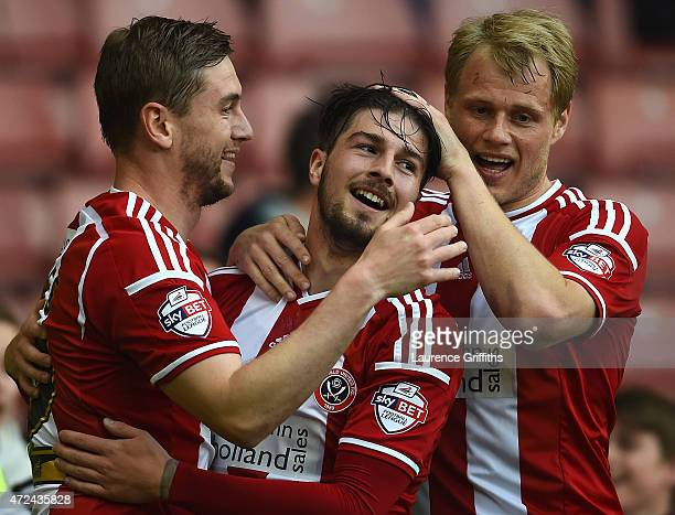 Kieron Freeman of Sheffield United battles is congratulated on scoring the opening goal by Steven Davies and Jay McEverley during the Sky Bet League...