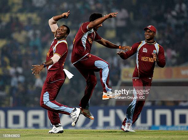 Kieron Pollard and Ravi Rampaul of West Indies celebrate the wicket of Luke Wright of England during the A1 versus B2 Super Eight match between...