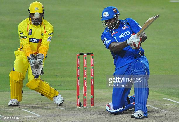 Kieron Pollard of Mumbai hits another six with MS Dhoni of CSK looking on during the Karbonn Smart CLT20 match between Chennai Super Kings and Mumbai...