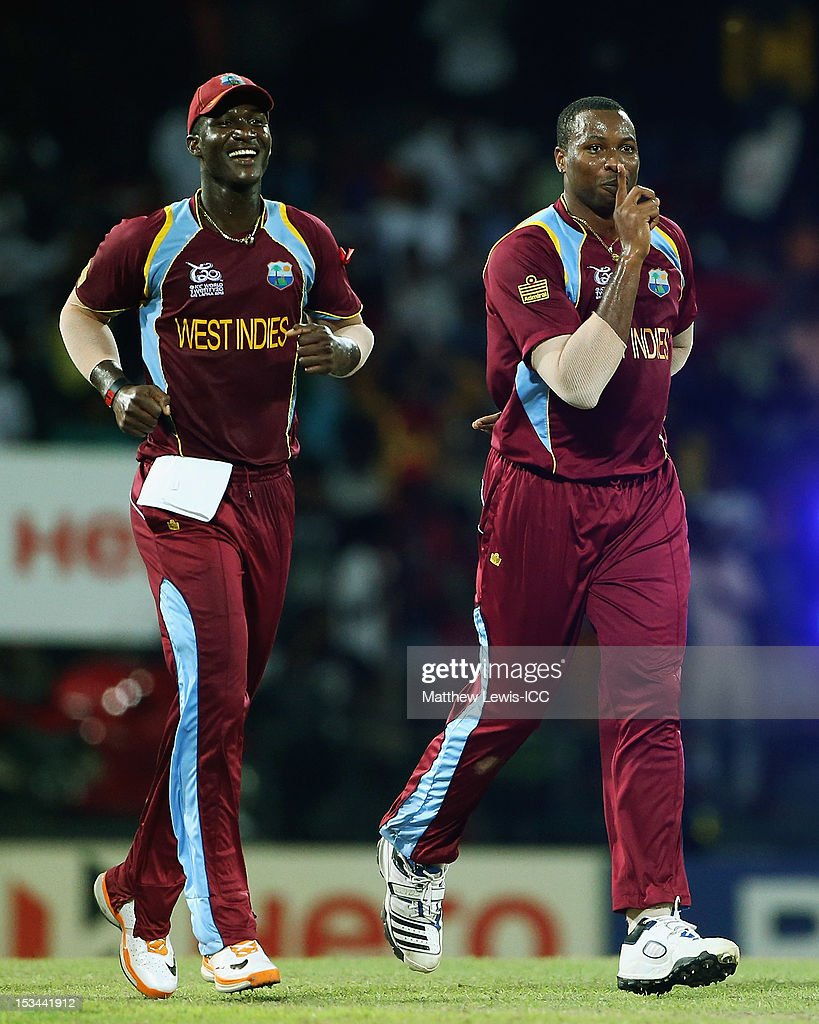 <a gi-track='captionPersonalityLinkClicked' href=/galleries/search?phrase=Kieron+Pollard&family=editorial&specificpeople=4233862 ng-click='$event.stopPropagation()'>Kieron Pollard</a> of the West Indies celebrates the wicket of Pat Cummins of Australia with <a gi-track='captionPersonalityLinkClicked' href=/galleries/search?phrase=Darren+Sammy&family=editorial&specificpeople=2920912 ng-click='$event.stopPropagation()'>Darren Sammy</a>, after he was caught by Johnson Charles during the ICC World Twenty20 2012 Semi Final match between Australia and West Indies at R. Premadasa Stadium on October 5, 2012 in Colombo, Sri Lanka.