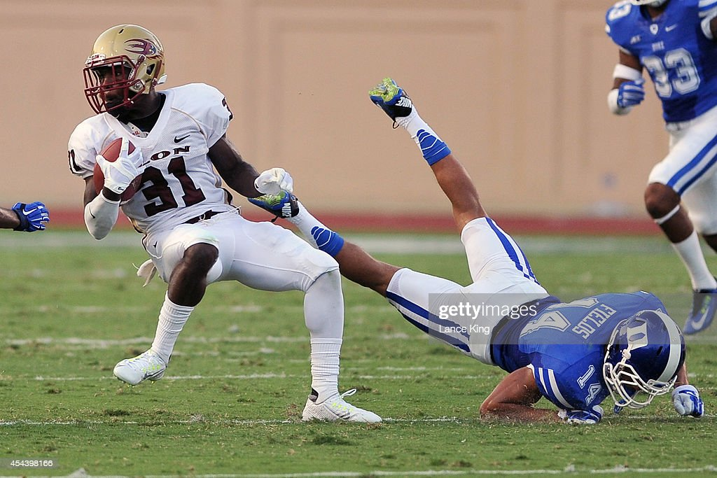 Kierre Brown #31 of the Elon Phoenix avoids a tackle by Bryon Fields #14 of the Duke Blue Devils at Wallace Wade Stadium on August 30, 2014 in Durham, North Carolina.