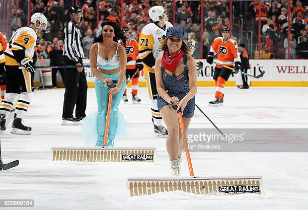 Kiersten Helsel and Kennedy McCabe of the Philadelphia Flyers ice girls clean the ice during a timeout against the Pittsburgh Penguins on October 29...