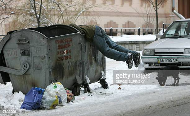 A stray dog eats while a homeless man searches a refuse bin in the center of Kiev 08 February 2007 AFP PHOTO/ SERGEI SUPINSKY