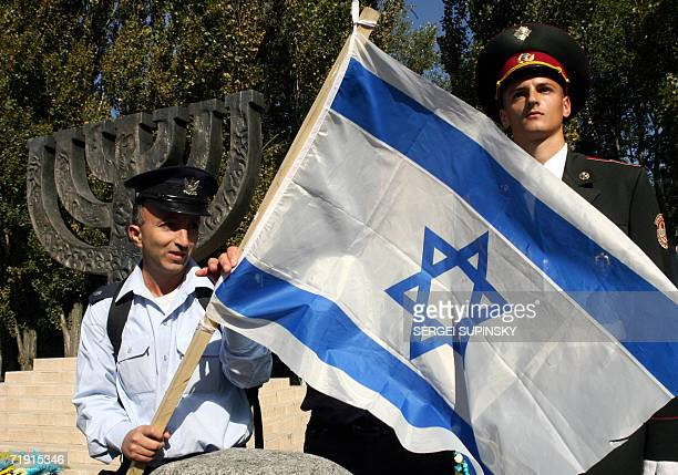 An Israeli soldier holds his national flag while an Ukrainian soldier stands guard during a commemorative ceremony near the Minora monument to...