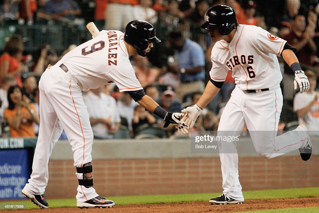 Kike Hernandez #6 of the Houston Astros receives a low five from Marwin Gonzalez #9 after hitting a home run in the fifth inning against the Seattle Mariners at Minute Maid Park on July 2, 2014 in Houston, Texas.