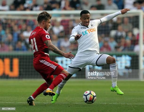 Kiko Femenia of Watford challenges Matrin Olsson of Swansea City during the Premier League match between Swansea City and Watford at The Liberty...