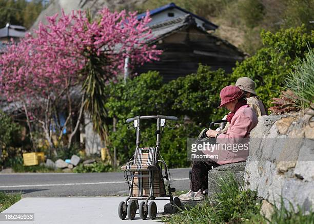 Kiku Sakakibara front and Tsutako Hashimoto sit by the side of a road on Gogo Island in Matsuyama Ehime Prefecture Japan on Friday March 22 2013 A...