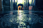 Focus on wet ground along dark medieval alley on a rainy night, Butter Slip, Kilkenny Ireland.