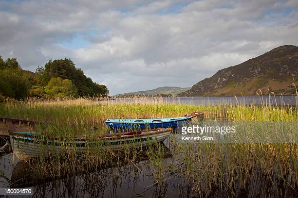 An afternoon landscape of a lake with rowboats in the foreground.