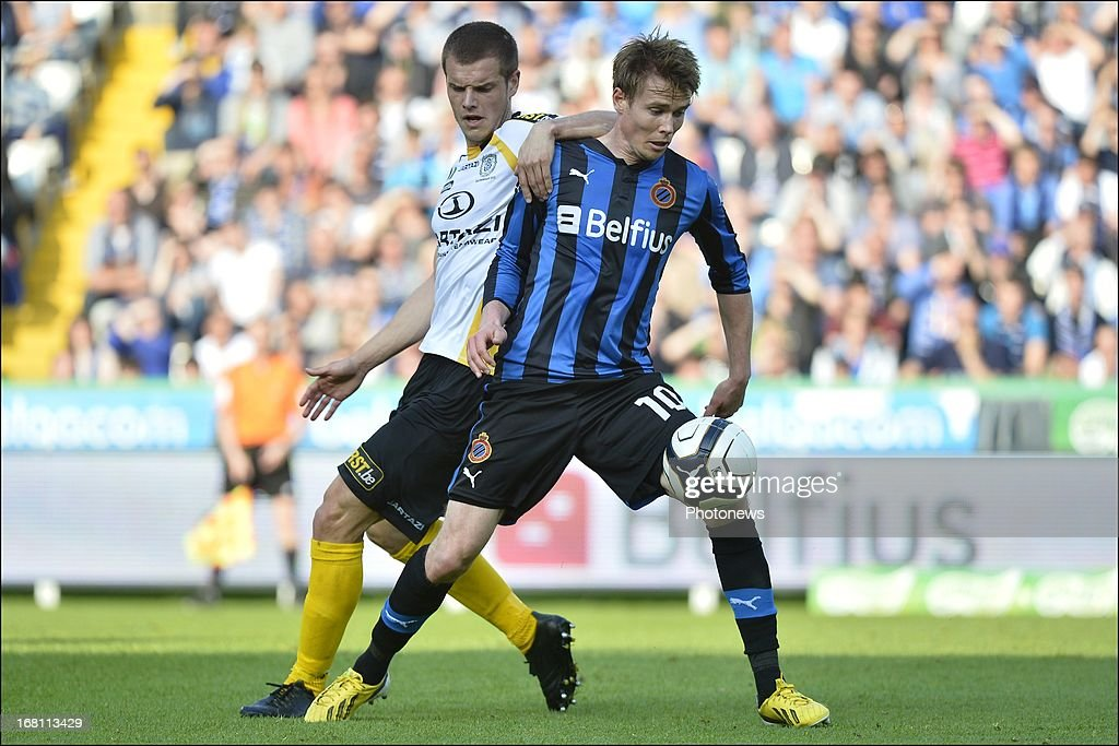Killian Overmeire of Sporting Lokeren OVL battles for the ball with Jesper Jorgensen of Club Brugge KV (R) during the Jupiler Pro League play-off 1 match between Club Brugge and Sporting Lokeren on May 5, 2013 in Brugge, Belgium.