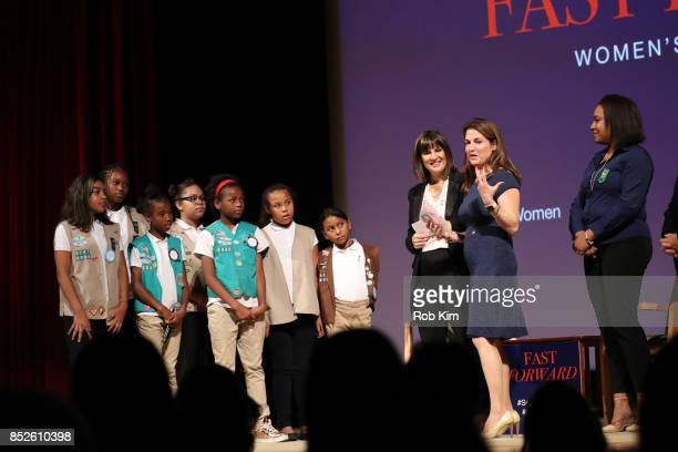 Kim Azzarelli Seneca Women Dr Joan LaRovere Vice President Virtue Foundation and Giselle Burgess Leader Troop 6000 stand on stage with the girls from...