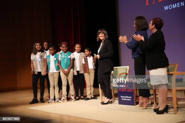 Kim Azzarelli Seneca Women Giselle Burgess Leader Troop 6000 and Meredith Maskara CEO Girl Scouts of Greater New York stand on stage with the girls...