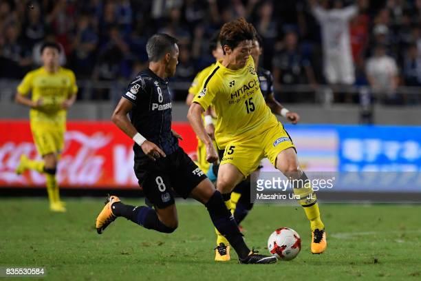 Kim Bo Kyung of Kashiwa Reysol controls the ball under pressure of Yosuke Ideguchi of Gamba Osaka during the JLeague J1 match between Gamba Osaka and...