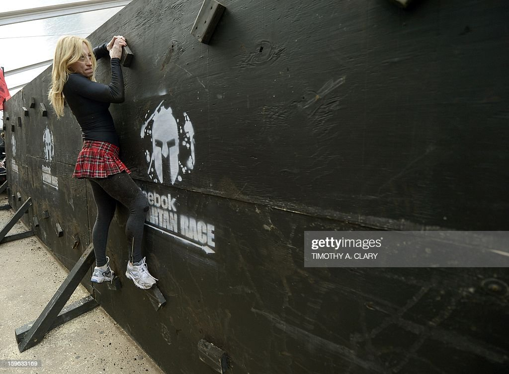 Kim Bruno tries an obstacle course on January 17, 2013, during a demonstration for the 'Spartan Race' scheduled for April 2013. The 'Spartan Race Times Square Challenge' demonstration and news conference was held at Times Square in New York to launch the multi-year business partnership between Reebok and Spartan Race.