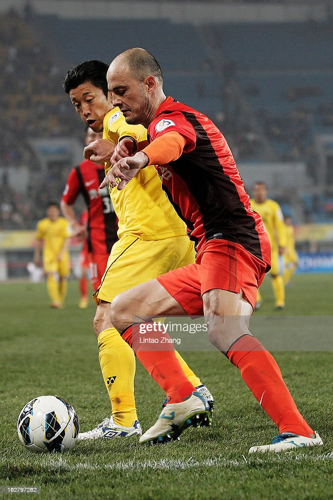 Kim Chang Soo (L) of Kashiwa Reysol challenges Victoriano Rivas Alvaro of Guizhou Renhe during the AFC Champions League match between Guizhou Renhe and Kashiwa Reysol at Olympic Sports Center on February 27, 2013 in Guiyang, China.
