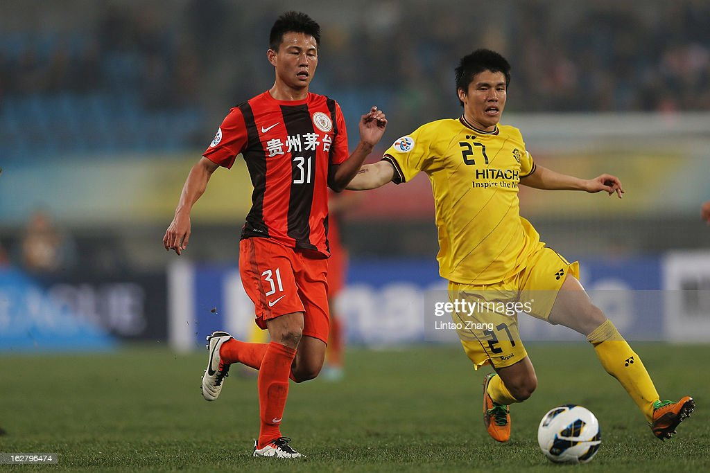 Kim Chang Soo (L) of Kashiwa Reysol controls the ball with Rao Weihui of Guizhou Renhe during the AFC Champions League match between Guizhou Renhe and Kashiwa Reysol at Olympic Sports Center on February 27, 2013 in Guiyang, China.